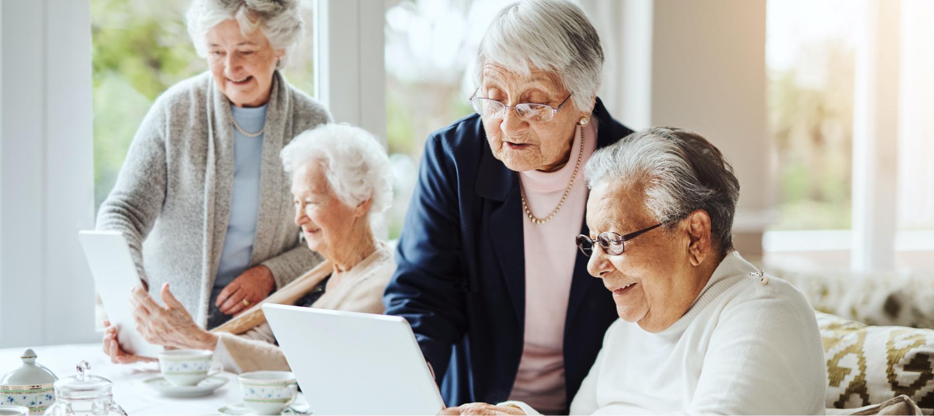 Seniorengruppe sehen sich etwas am Tablet an.