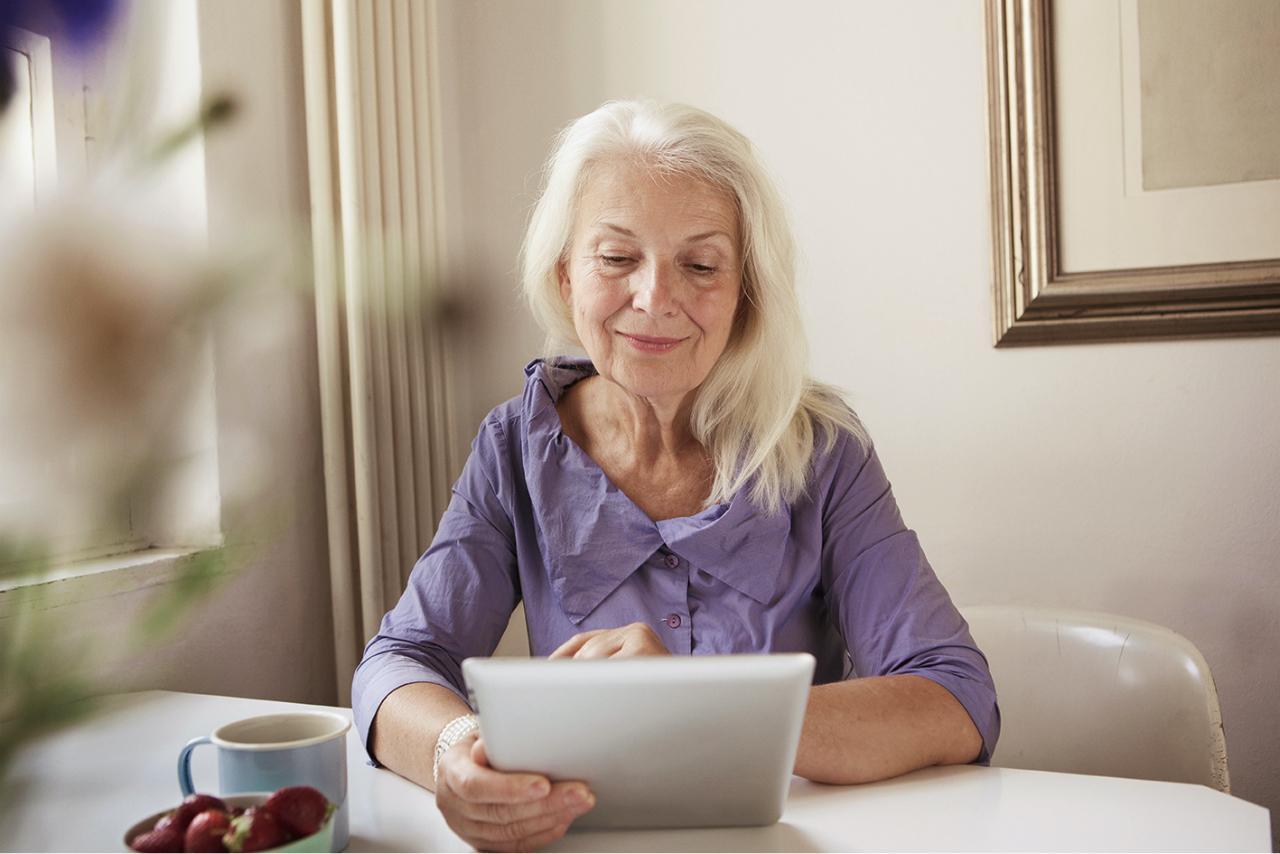 Seniorin sieht sich etwas am Tablet an