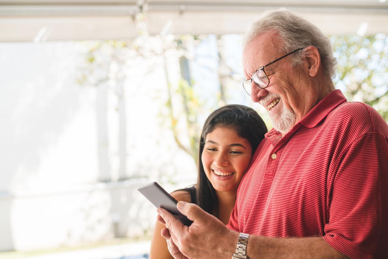 Älterer Herr und Enkelin sehen sich etwas am Tablet an