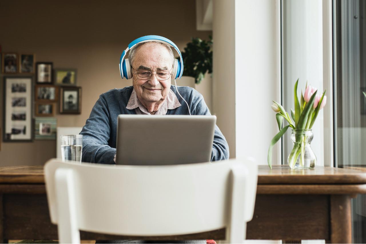 Älterer Herr mit Kopfhörern sieht sich etwas sam Laptop an